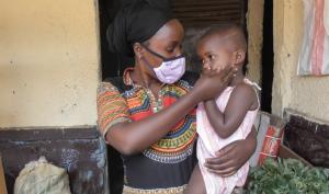une femme travaille sur le marché de Kigali avec son enfant dans les bras